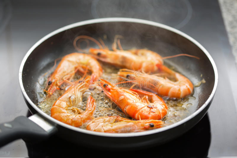 Fresh shrimps being fried in olive oil. Very shallow DOF stock photo