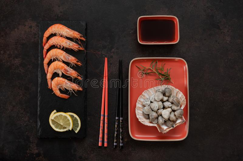 Fresh shrimps in black stone deck with lemon and raw Surf chamelea gallina in the scallop shell in orange dich and soy sauce. In Asian style with chopsticks on stock photography