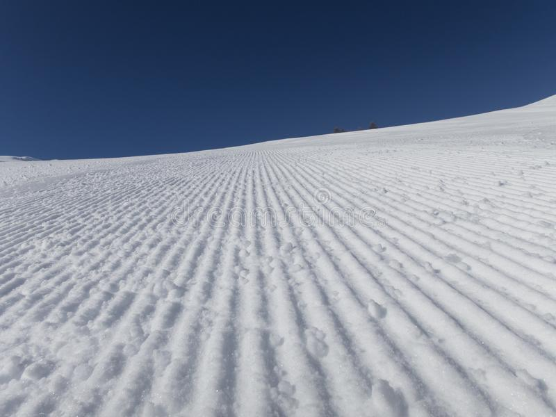 Fresh ski slopes early morning. And blue sky skiing alps French royalty free stock photo