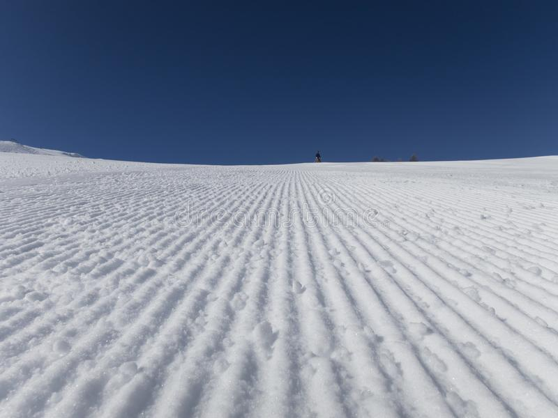 Fresh ski slopes early morning. And blue sky skiing French alps royalty free stock photo