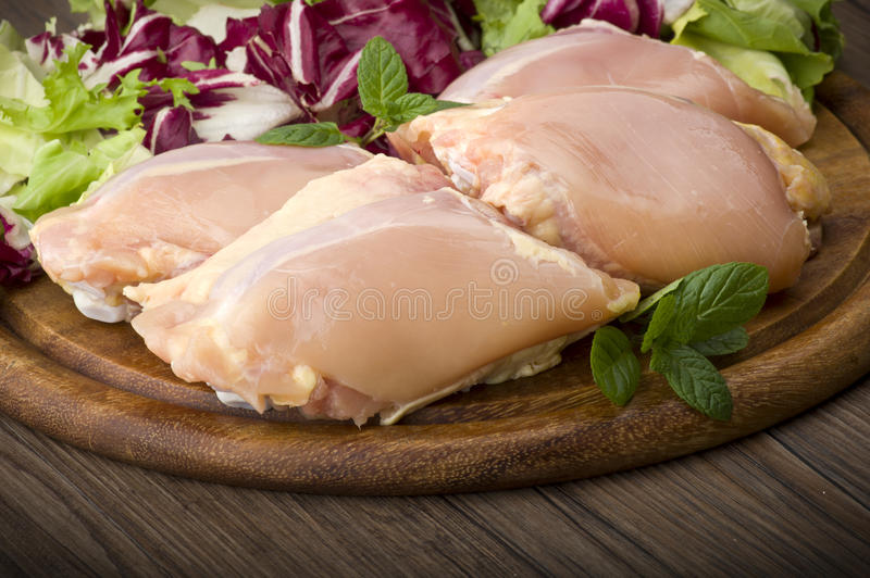 Fresh skinless chicken. Thighs and legs on cutting board stock photo