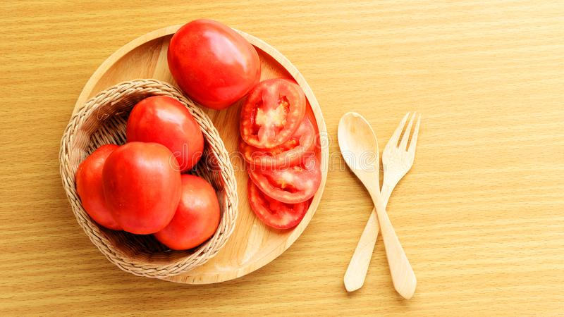 Fresh and slice tomatoes placed on a wooden plate. Spoon and fork lay on a wooden table. Cooking ingredient. Breakfast preparing a royalty free stock image