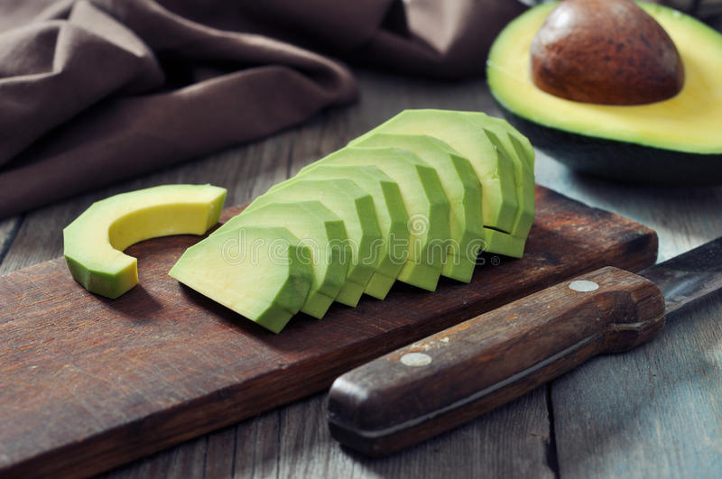Fresh sliced avocado. On cutting board over wooden background royalty free stock photos