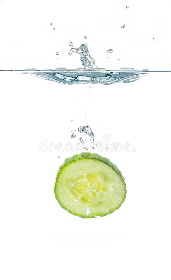Fresh sliced cucumber in water isolated on white background. One slice stock photos