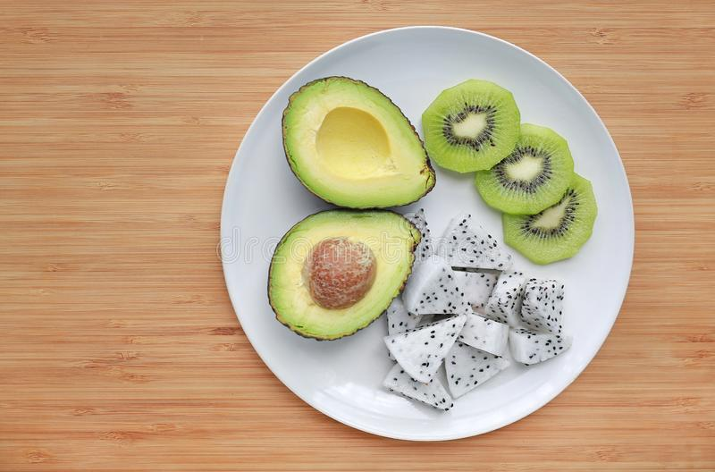 Fresh sliced fruit avocado, dragon fruit and kiwi on white plate against wooden board background with copy space stock photos