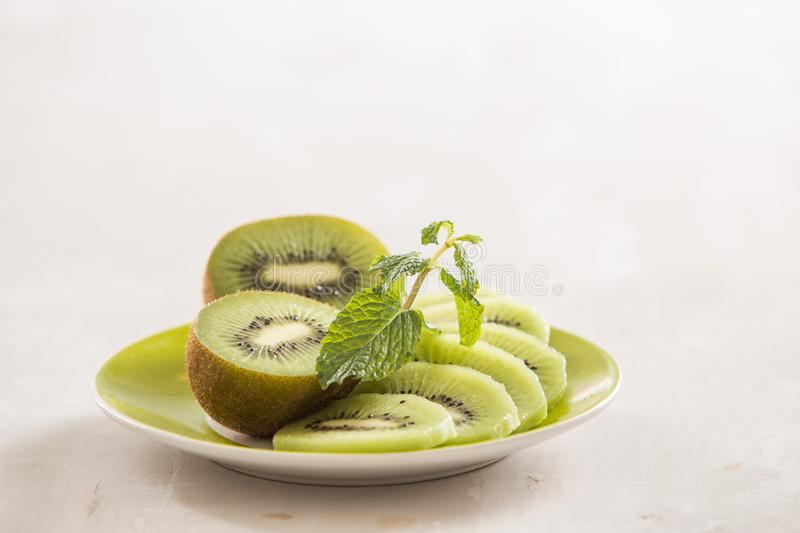 Fresh sliced kiwi on plate. Green Kiwi fruit slices on white wooden background. Copy space. Kiwi cuted on plate stock image