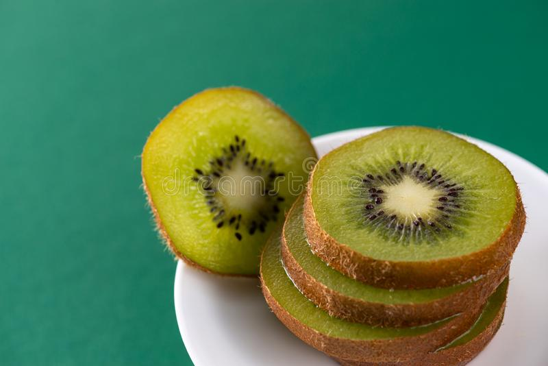 Delicious fresh sliced kiwi in a white plate on a green background stock images