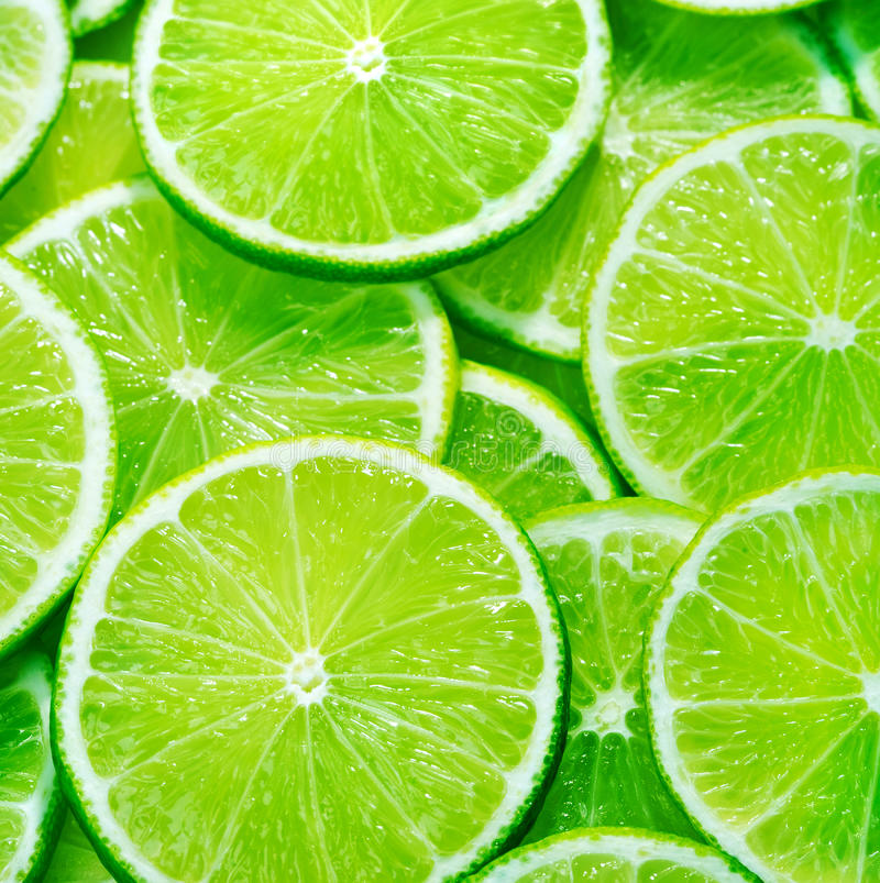 Fresh sliced limes. A background of fresh sliced limes stock image