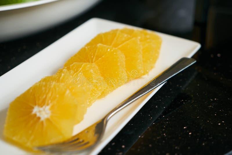 Fresh sliced orange plate with fork on black kitchen table stock photo