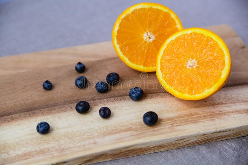Orange and blueberries on Wooden Cutting Board stock images