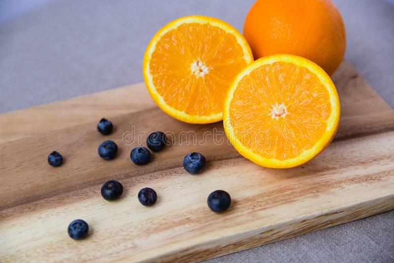 Orange and blueberries on Wooden Cutting Board stock photos