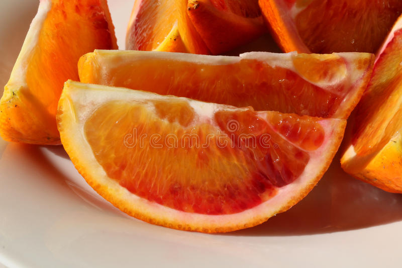 Fresh sliced Organic Blood Oranges on a plate. Organically grown Blood oranges from an Australian garden sliced and placed on a white plate royalty free stock images