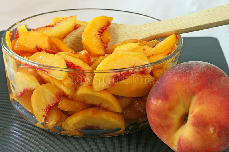 Fresh Sliced Peaches. In glass bowl with wooden spoon royalty free stock photo