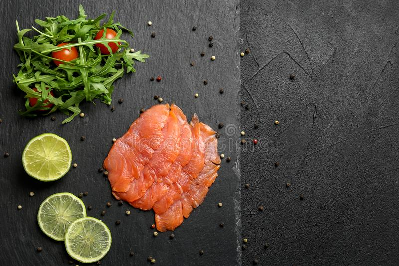 Fresh sliced salmon fillet with arugula and lemon on slate plate, top view stock image