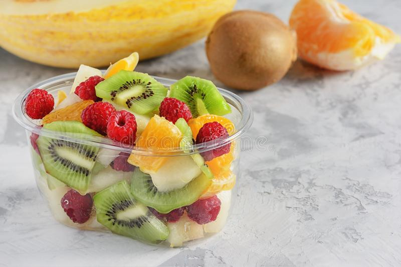 Fresh Sliced Tropical Fruits Berries in Container royalty free stock photography