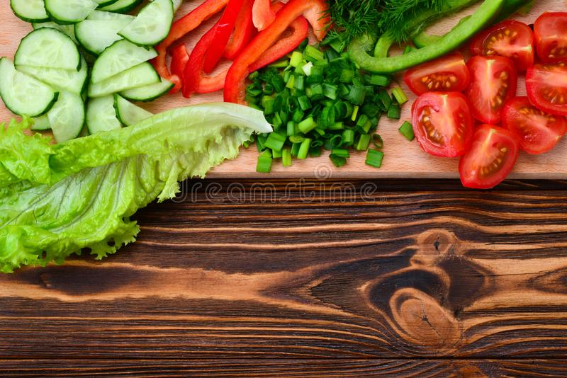 Fresh sliced vegetables on a salad: radish, cherry, greens, cucumber, red pepper. stock images