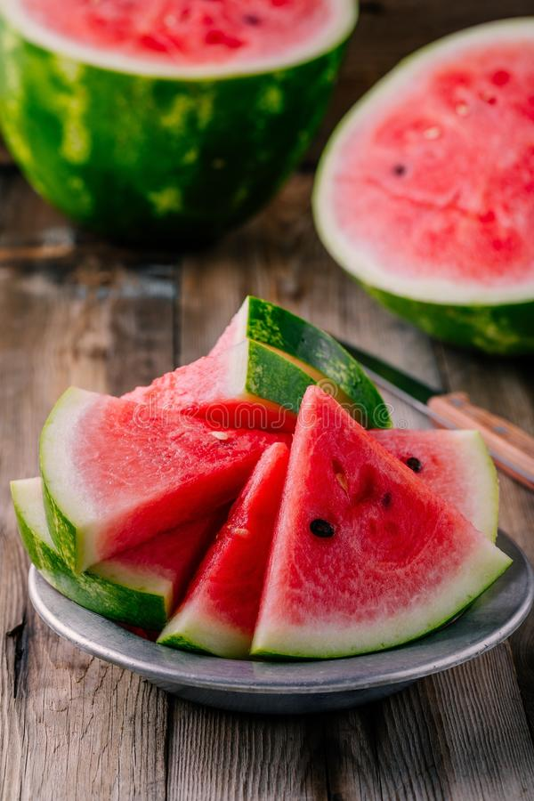 Fresh sliced watermelon on wooden rustic background. Fresh ripe sliced watermelon on wooden rustic background royalty free stock photo