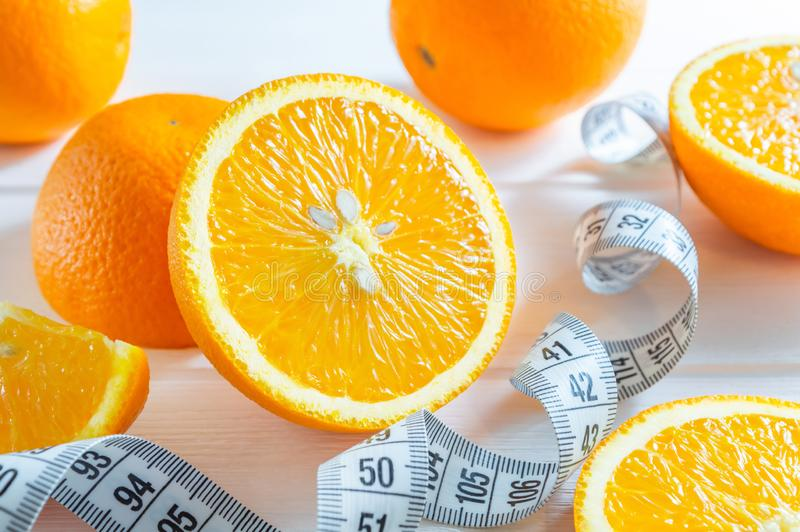 Fresh sliced and whole oranges, and measuring tape on white wooden table royalty free stock images