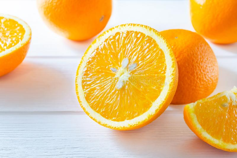 Fresh sliced and whole oranges on white wooden table stock photos