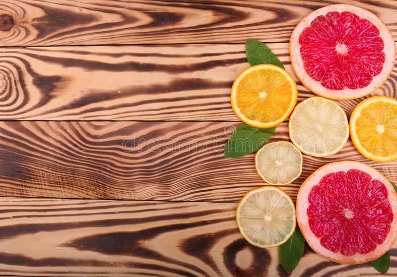 Fresh slices of juicy orange, ripe lemon, and organic grapefruit with leaves of mint on a wooden background, top view. stock photos