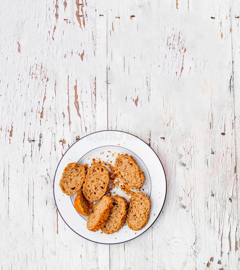 Fresh slices of whole bran bread on a white plate on rustic whit royalty free stock photo