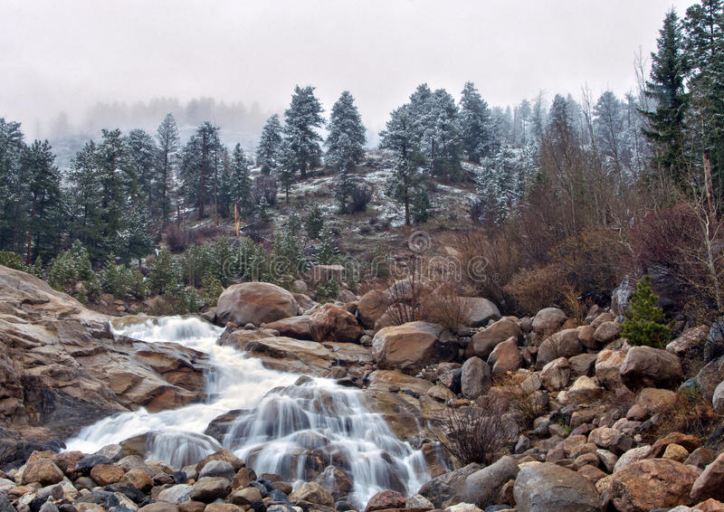 Fresh snow and waterfall in the Rocky Mountain National Park. Fresh snow dusts the landscape over the Horseshoe Falls on the Alluvial Fan Trail in the Rocky royalty free stock photo