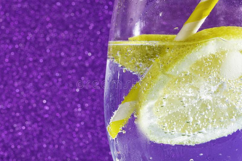 Soda on shiny purple. Fresh soda with bubbles an ice cube, a  slice of lemon and a straw on a shiny purple background. Free space for text royalty free stock image