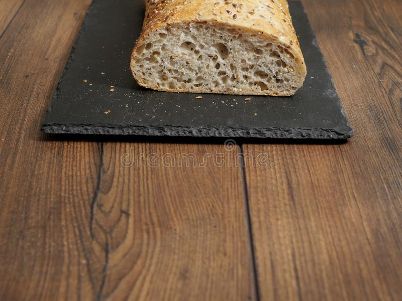 Fresh sourdough bread on a slate black plate. Fresh sourdough bread on a black slate plate on wooden table. Copy space stock photography