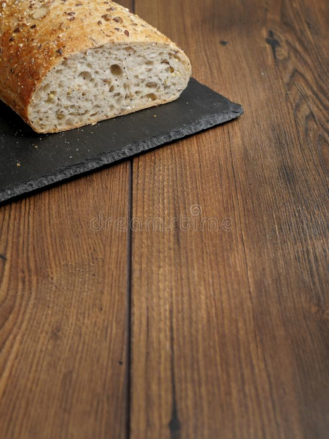 Fresh sourdough bread on a slate black plate. Fresh sourdough bread on a black slate plate on wooden table. Copy space royalty free stock image
