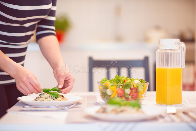 Fresh spaghetti with creamy mushroom sauce and basil leaf. In home interior stock images