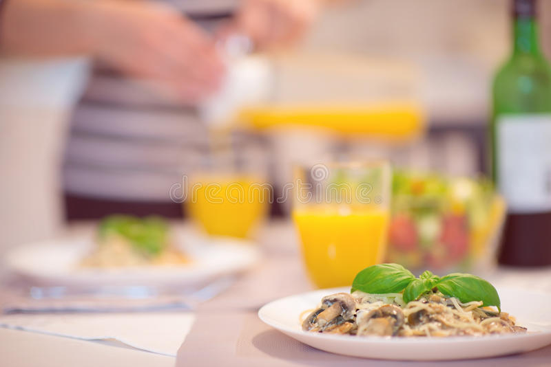 Fresh spaghetti with creamy mushroom sauce and basil leaf. In home interior royalty free stock photography