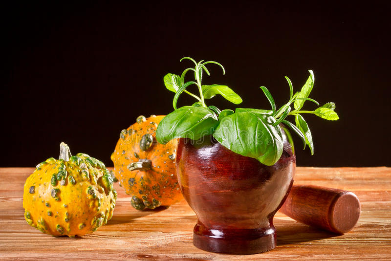 Fresh spices in wooden mortar with orange pumpkins stock photography