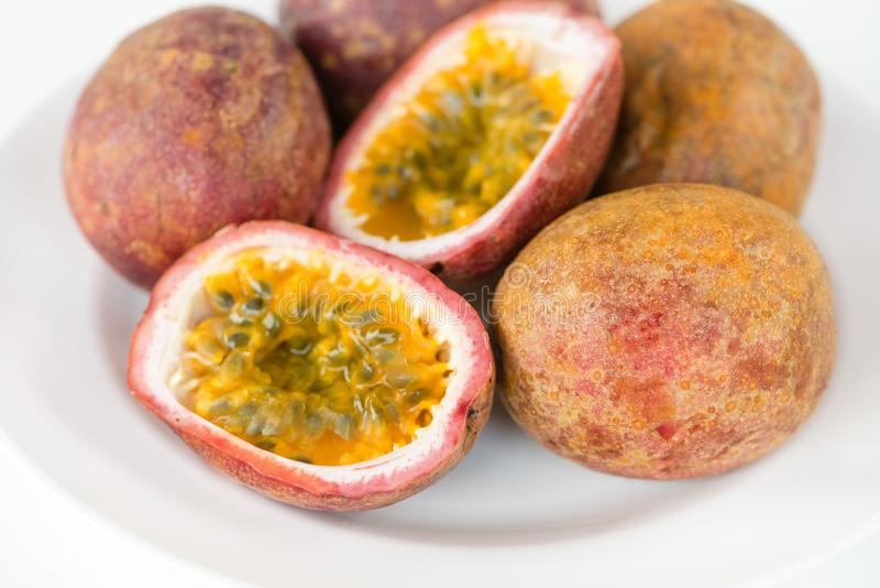 Fresh splitted passion fruits. Fresh cut and split fresh juicy passion fruits on white plate stock image