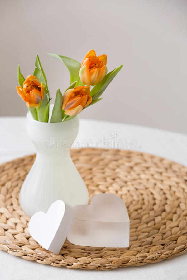 Fresh spring bunch of orange tulips in a nice white glass vase and two cute heart symbols on the straw board. Home decor for stock photos