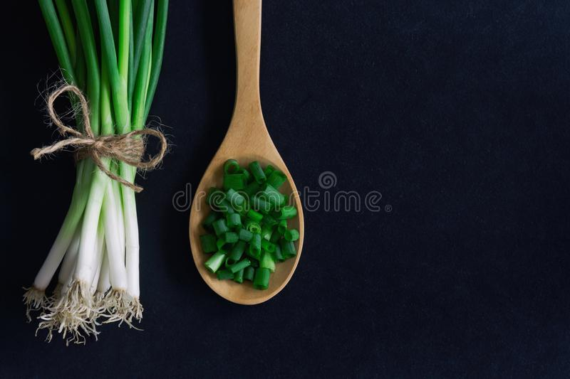 Fresh spring onion on black granite table. Close up on chopped c stock photos