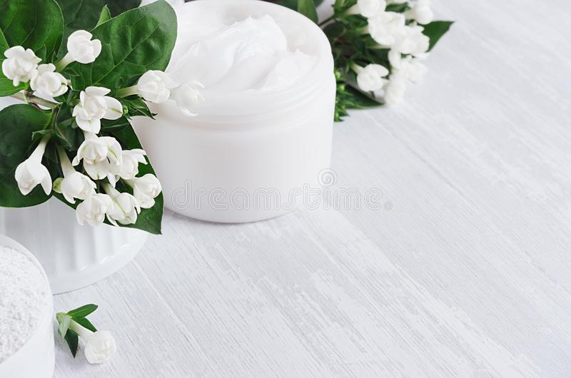 Fresh spring organic spa cosmetics products with small white flowers and green leaves on white wood background, copy space. stock photos