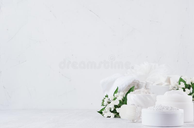 Fresh spring organic spa cosmetics products with small white flowers and green leaves on white wood background, copy space. stock images