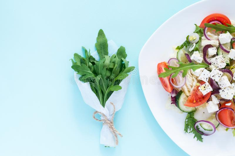 Fresh spring salad with cucumber, tomato, cheese and arugula isolated on a white plate. And Bouquet of fresh green arugula leaves on a light blue background royalty free stock image