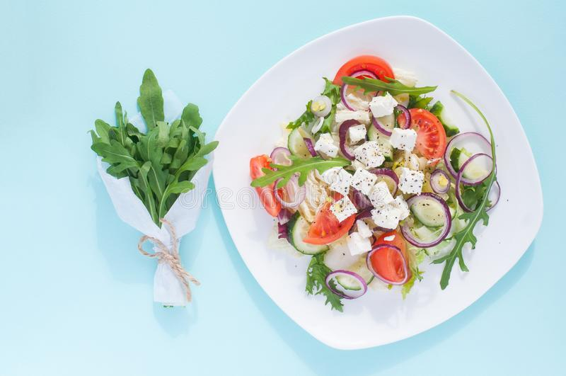 Fresh spring salad with cucumber, tomato, cheese and arugula isolated on a white plate. And Bouquet of fresh green arugula leaves on a light blue background royalty free stock photo