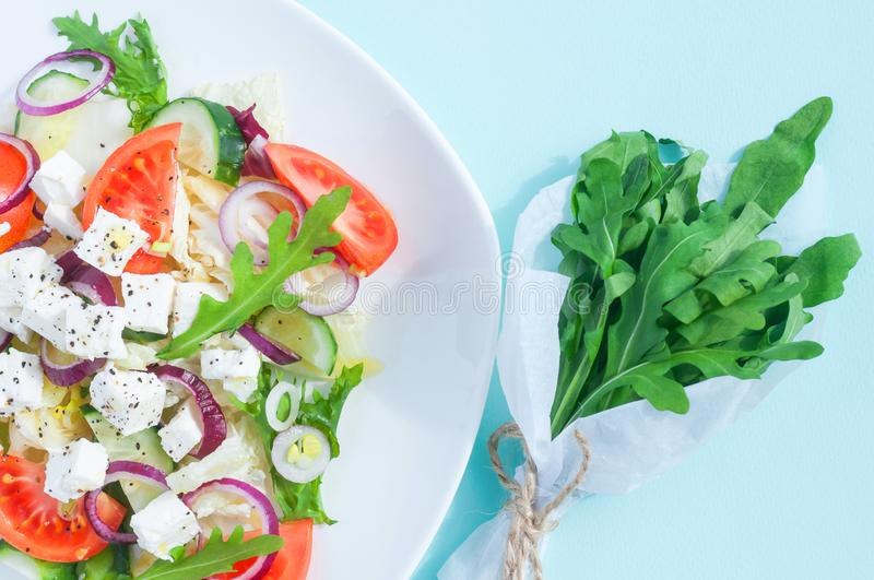 Fresh spring salad with cucumber, tomato, cheese and arugula isolated on a white plate. And Bouquet of fresh green arugula leaves on a light blue background royalty free stock photography
