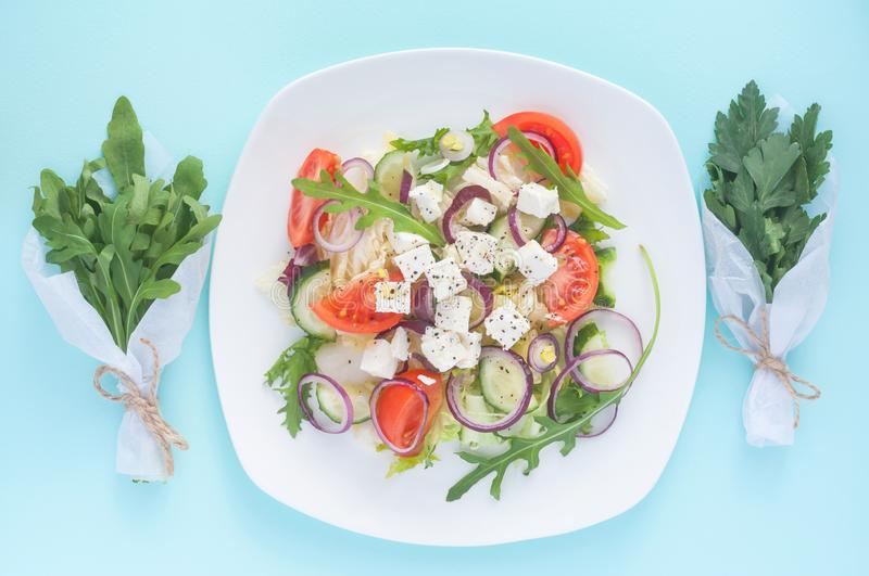 Fresh spring salad with cucumber, tomato, cheese and arugula isolated on a white plate. And Bouquet of fresh green arugula leaves and parsley leaves on a light stock photos