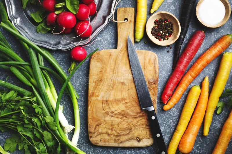 Fresh spring vegetables around wooden cutting board with kitchen knife for vegetarian cooking stock photography