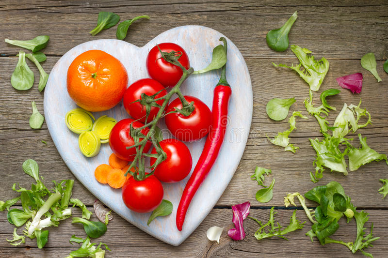 Fresh spring vegetables on wooden heart royalty free stock photos