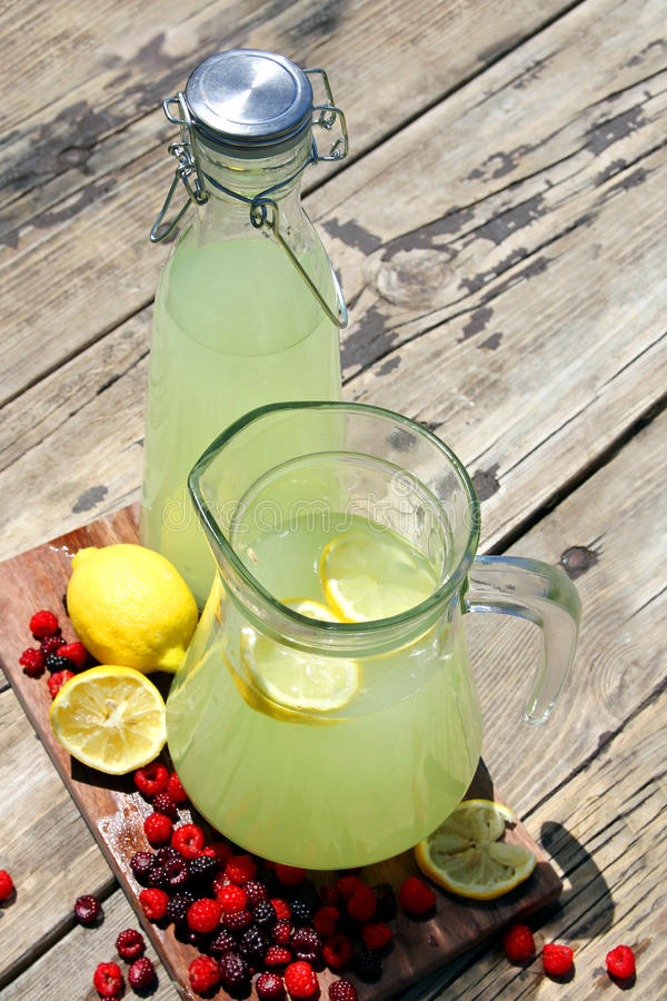 Fresh Squeezed Lemonade in Pitchers with Raspberry Fruit stock images