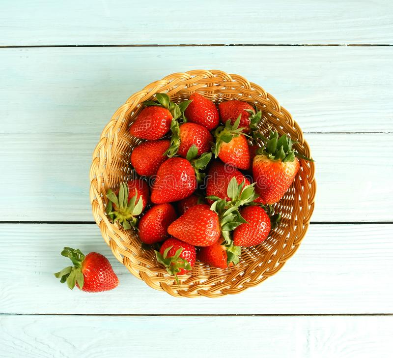 Fresh strawberries in a basket on a blue wooden background top view stock photo