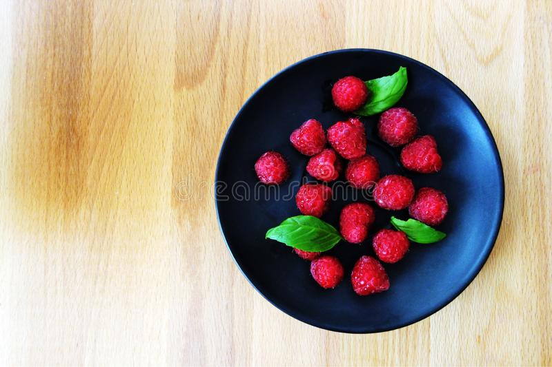 Fresh strawberries on black plate and wooden board flat lay royalty free stock photos