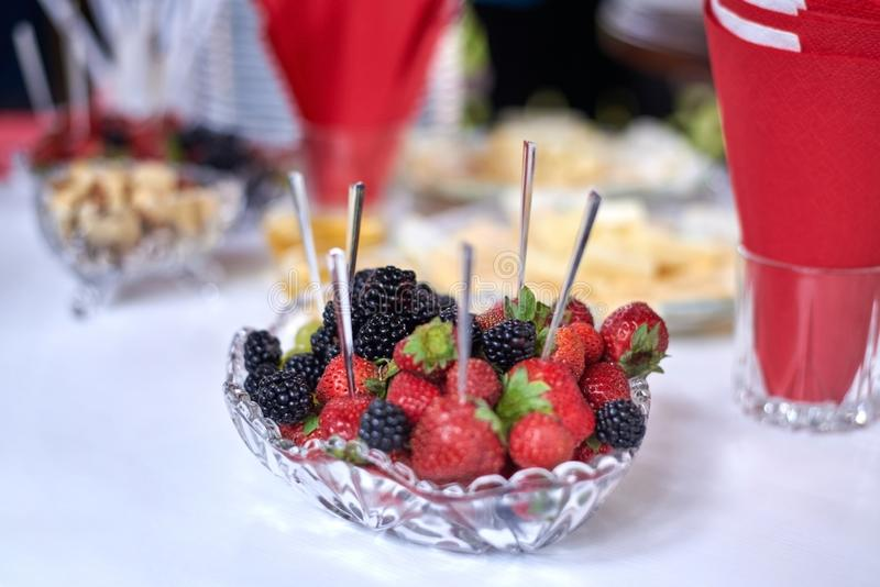 Strawberries and blackberries on skewers laid out on a plate on a served table stock photo
