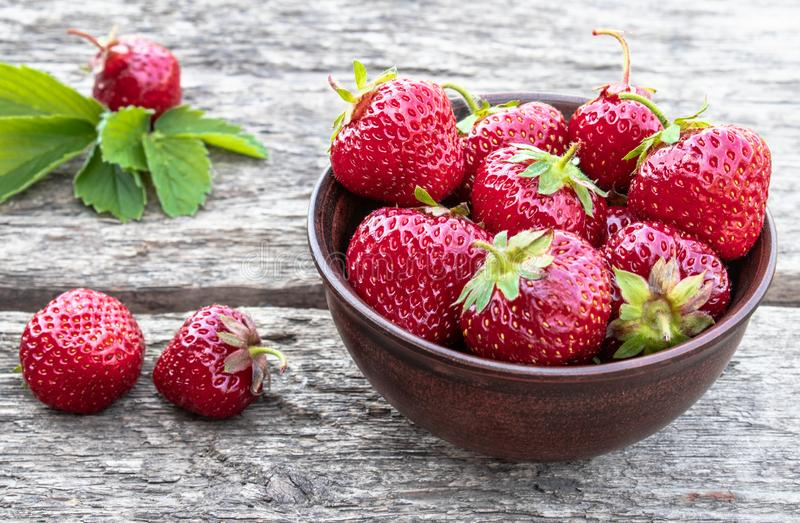 Fresh strawberries in a bowl on a wooden table stock photography