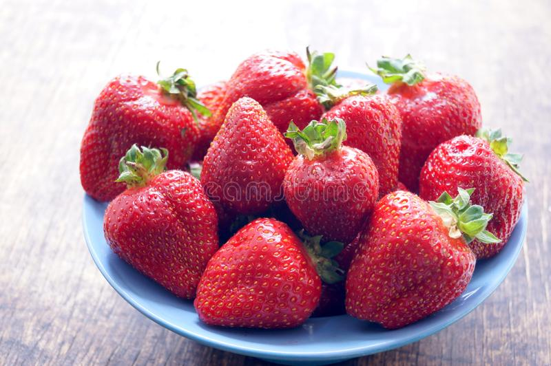 Fresh strawberries in a bowl on a wooden table. Fresh strawberries in a bowl on a wooden table. Vegetarianism, vegan royalty free stock photography
