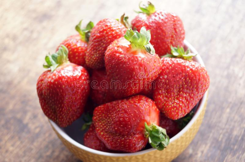 Fresh strawberries in a bowl on a wooden table. Fresh strawberries in a bowl on a wooden table. Vegetarianism, vegan royalty free stock images